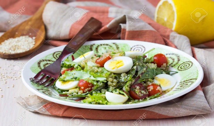 Healthy quinoa salad with tomatoes, avocados, eggs, herbs, lettuce, lemon, diet dish