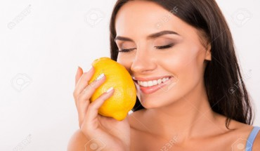 sexy beautiful young woman sniffing the scent of lemon